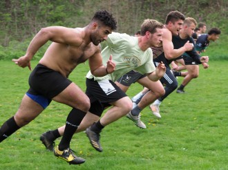 Rugby players line up to run a sprint.