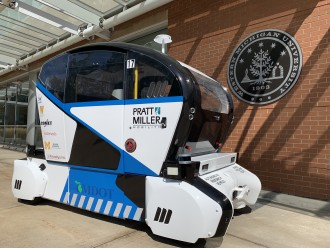 Photo of a blue and white autonomous vehicle next to a brick wall featuring Western Michigan University's seal.