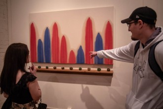 Andrew Simpkins points at his painting which uses red and blue paint to signify pesticides found in tomatillos.