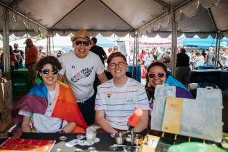 Students sit at a rainbow-clad table for Kalamazoo Pride.