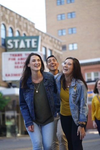 Students laugh together in front of the State Theatre sign.