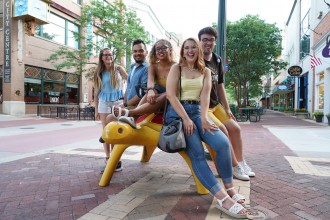 A group of students sits on a sculpture of a yellow turtle on a brick pedestrian mall.