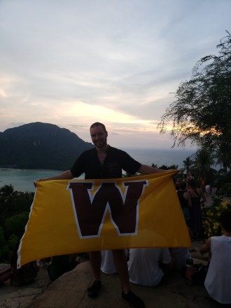 "Dylan Coleman holds a large gold flag with a brown ""W"" on it in a tropical setting."