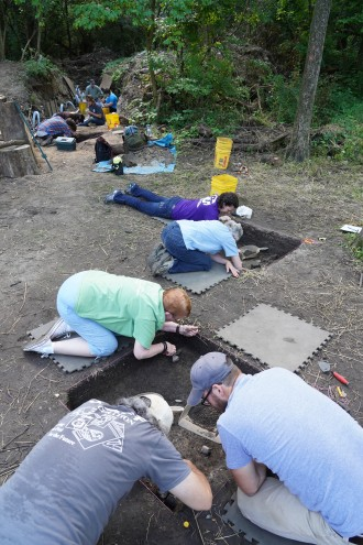 Several people use trowels to excavate in holes at an archaeological site.