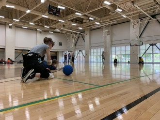 Athletes crouch in a gym to play goalball.