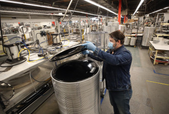A manufacturing employee lifts a drumhead off of a stack next to a production line.