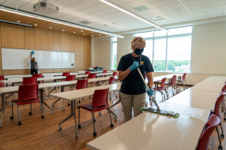 A custodian cleans a table in a classroom.
