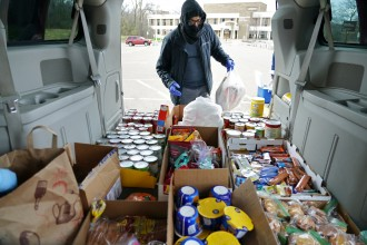 A student gets grocercies from inside a van.