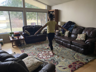 Jolin Cramer dances in her living room in front of her laptop where class is going on.