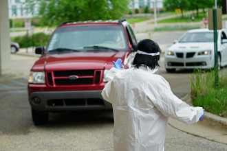 A person in a medical gown motions toward an SUV.