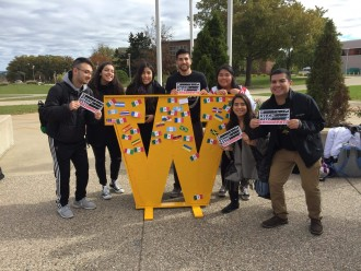 "students with WMU sign ""I stand with immigrants"""