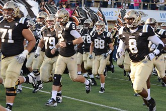 Photo of WMU football team running onto the field.