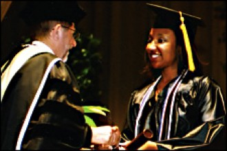 Photo of WMU President John M. Dunn congratulating a graduate.