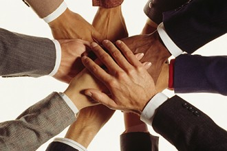 Photo of hands stacked in a huddle.