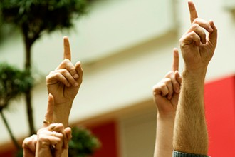 Photo of hands raised in a classroom.