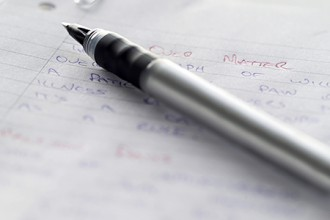 Photo of a pen on a page full of handwritten notes.