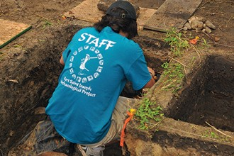 Photo of person excavating dirt at an archaeological site.