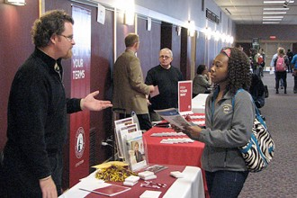 Photo of student speaking with university representative.