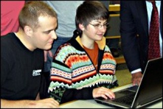 Photo of staff member helping student.