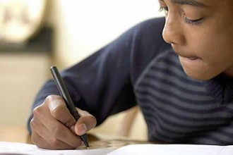 Photo of young boy writing.