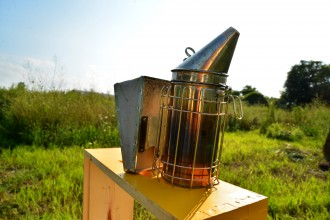 Photo of a bee smoker with a field in the background.