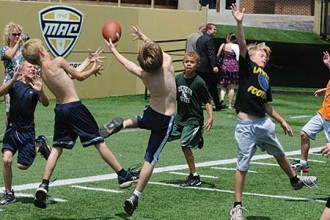 Photo of young boys playing football at summer camp.