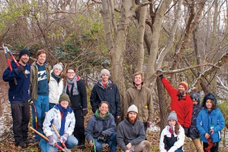 Photo of faculty, staff, students, alumni and volunteers in front of the large dwarf hackberry tree.