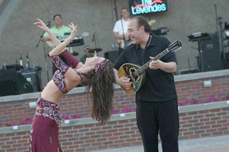 Photo of a band performing with a belly dancer.