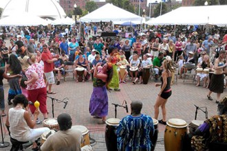 Photo of dancers and people playing African drums.