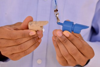 Photo of Daniel Floyd comparing a cork prototype to the SpeechMasterPro.