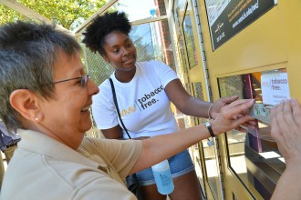 Photo of staff member and student posting no-smoking signs.