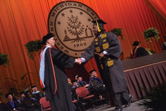 Photo of Dean Li congratulating a graduating student.