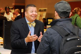 Photo of a staff member speaking with a student at a career fair.