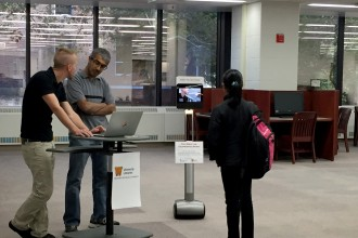 Photo of a student looking at the robot in Waldo Library.