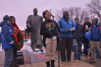 Photo of woman speaking in front of MLK statue.