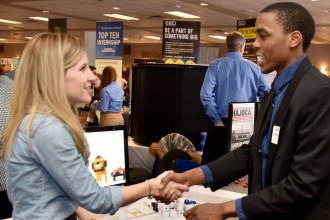 Photo of a student and a recruiter at a career fair.