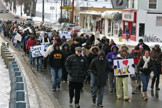 Photo of President John M. Dunn marching with students in an MLK Day march.