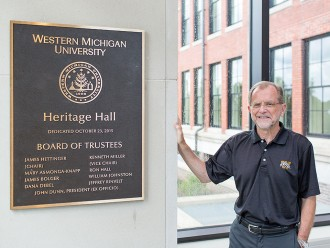 Photo of WMU President John M. Dunn with a dedication plaque for Heritage Hall.