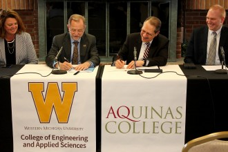 Photo of the WMU and Aquinas College's presidents signing an agreement between the two schools.