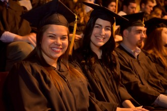 Photo of two female graduates in full regalia, seated during an WMU commencement ceremony.