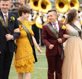 Four WMU students stand on the football field at Waldo Stadium wearing homecoming sashes.