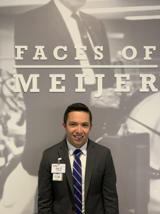 "A WMU alumnus stands in front of a sign that reads ""Faces of Meijer."""
