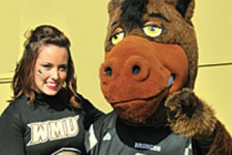 Photo of WMU cheerleader and Buster Bronco.