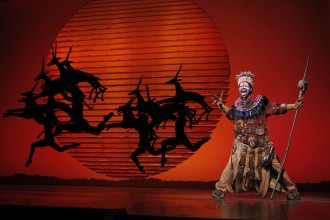 "Photo of Buyi Zama in costumeas Rafiki in the musical ""The Lion King."""