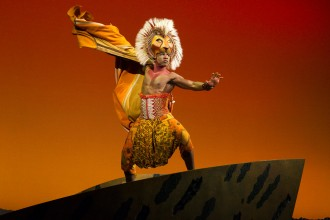"Photo of Dashaun Young in costume as Simba in the musical ""The Lion King."""
