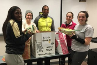 Photo of five WMU students from Phi Epsilon Kappa fraternity holding children's books donated for the campus United Way Book-It drive.