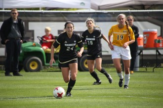 Photo of Bronco women's soccer player Alex Ruffer running down a field kicking a soccer ball followed by other players.