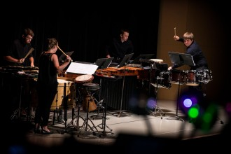 Photo of members of the Western Michigan University Percussion Ensemble playing various instruments on a stage.