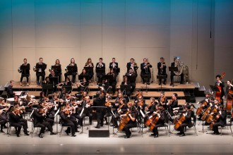Photo of musicians from the WMU Symphony Orchestra performing on a stage.
