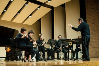 Photo of the Western Winds performing on stage with Conductor Scott Boerma.